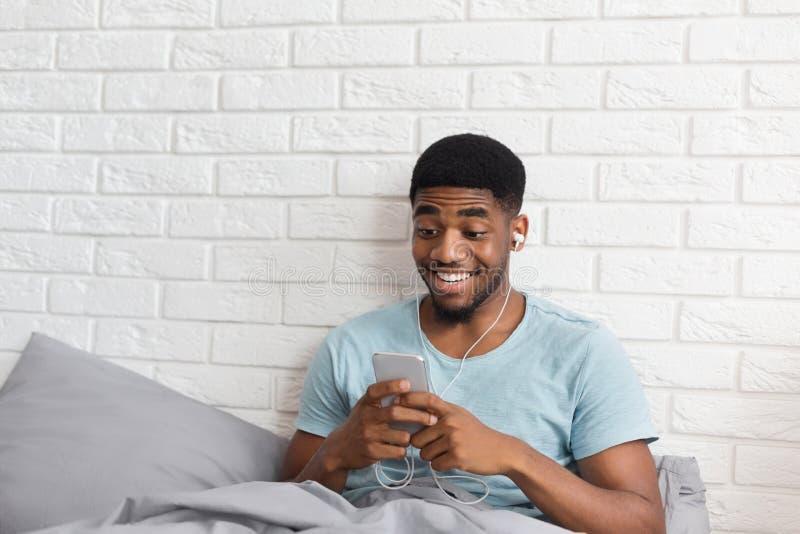 Black man enjoying video online on his smartphone royalty free stock image