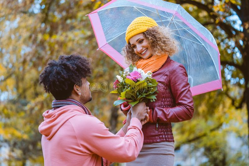 Black man proposing to Caucasian girl who happily accepts royalty free stock image