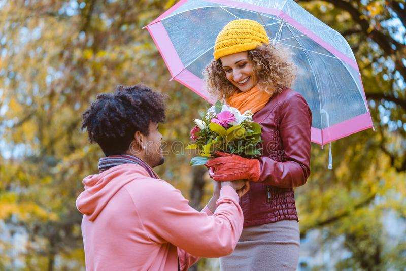 Black man proposing to Caucasian girl who happily accepts royalty free stock images