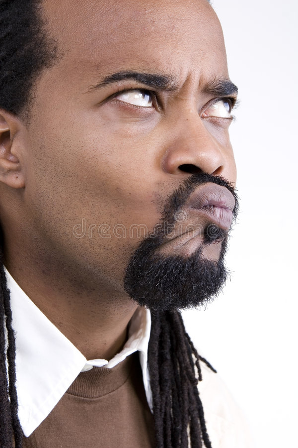 Black man pulling funny face. Side portrait of young black man pursing lips, looking upwards and pulling funny face; white background stock image