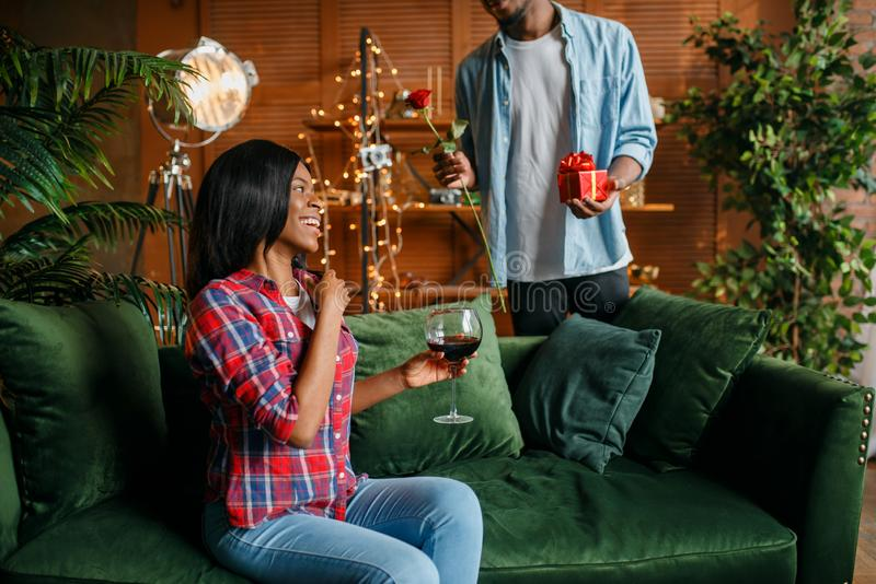Black man with red rose and gift behind his woman royalty free stock images