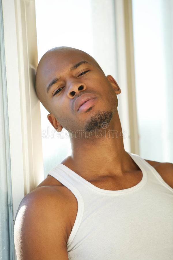 Black man relaxing by window at home royalty free stock photo