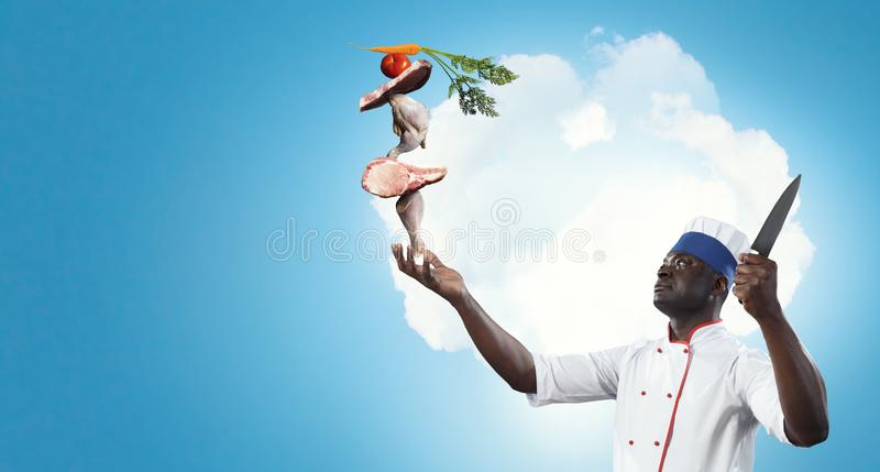 Black chef creative cooking. Mixed media. Black man self confident, holding a big kitchen knife with ingredients build into pyramid on his hand, blue cloudy sky royalty free stock photo
