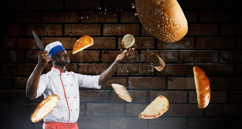 Black chef creative cooking. Mixed media. Black man self confident, holding a big kitchen knife with pieces of bread flying around him, brick wall dark stock image