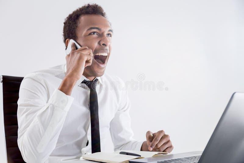 Black man shouting on phone stock image