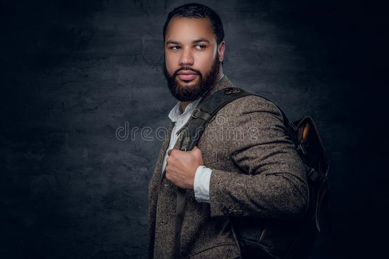 Black man in a suit holds backpack. Bearded black man in a suit holds backpack stock photo