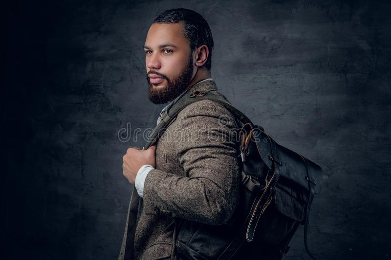 Black man in a suit holds backpack. Bearded black man in a suit holds backpack royalty free stock images
