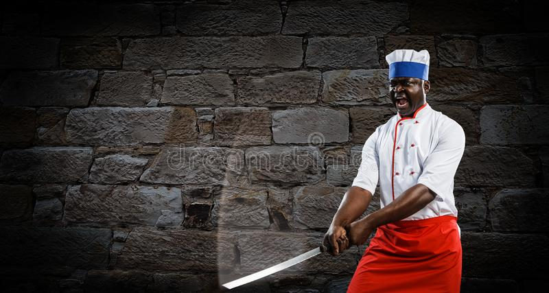 Black chef creative cooking. Mixed media. Black man triumphant, dramatic and victorous, holding a big kitchen knife, brick wall background royalty free stock photo