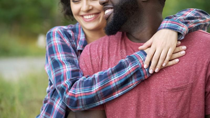 Black man and white woman smiling and tenderly hugging, happy people together royalty free stock images