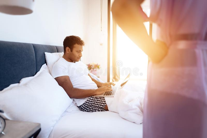 Black man and woman in the bedroom. A man is lying on the bed with laptop. Before him is his girl in lingerie. Black men and women in the bedroom. A men is royalty free stock image