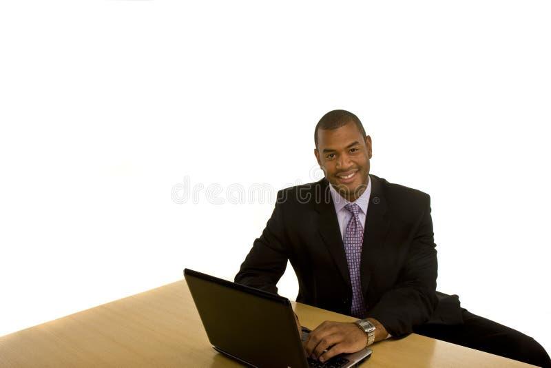 Black Man Working on Laptop Smiling at Camera royalty free stock photography