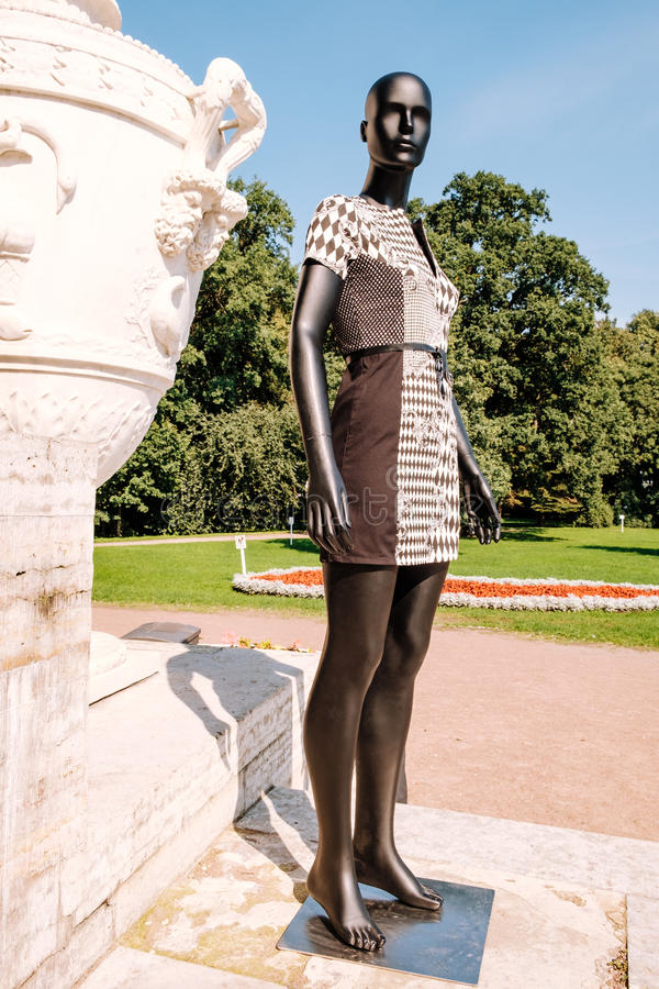 Black mannequin dressed in a dress. Black mannequin dressed in a beautiful dress in the park stock photos