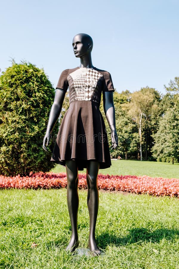 Black mannequin dressed in a dress. Black mannequin dressed in a beautiful dress in the park stock image