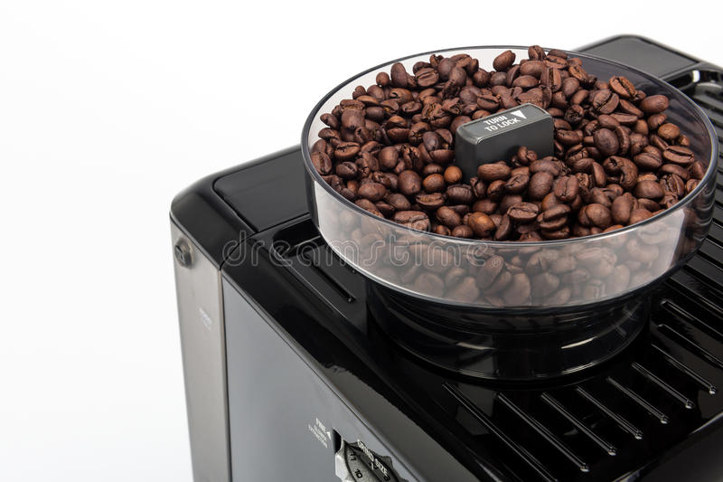 Black manual coffee maker on white background, grinder with fresh coffee beans detail top view stock images
