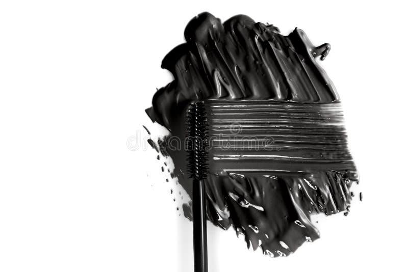 Black mascara brush stroke with applicator brush isolated on white royalty free stock photo