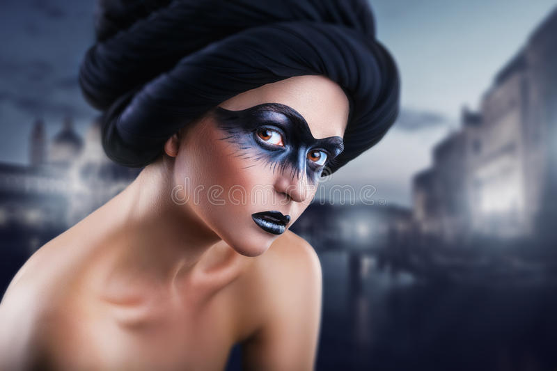 Black mask. Portrait of a young woman with a make-up black mask on the background of the city at night. Fashion make-up. Black mask royalty free stock image
