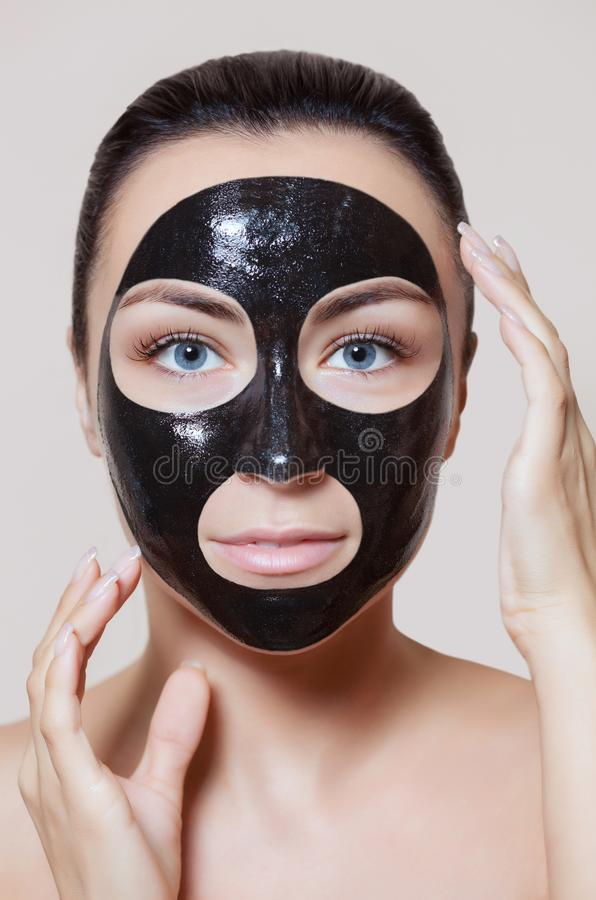 A black mask to the face of a beautiful woman. Spa treatments and care of the cats. In the beauty salon royalty free stock photography