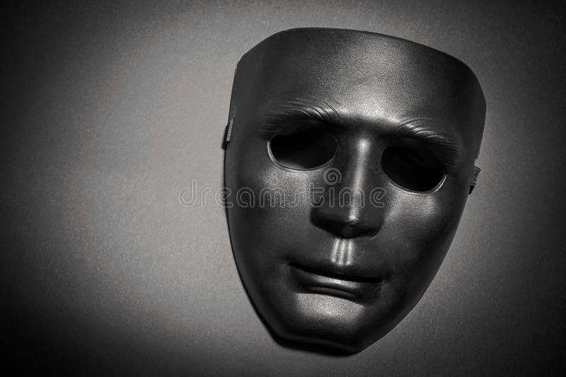 Black mask under a ray of light. On a gray background royalty free stock photography