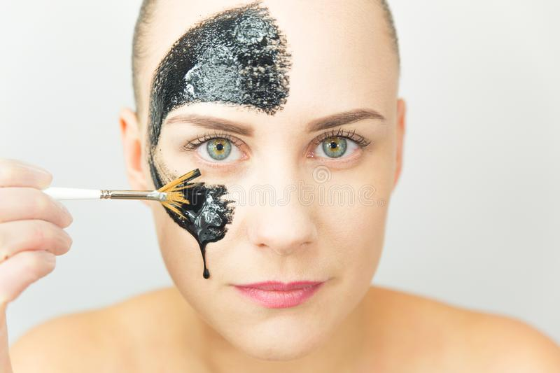 Black mask. Woman with purifying black mask on her face royalty free stock image
