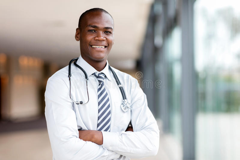 Black medical doctor. Good looking black medical doctor with arms crossed stock photo