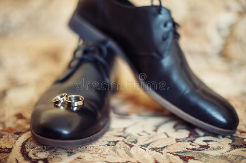 Black men shoes and wedding rings stock photo