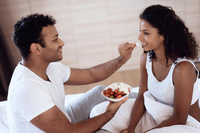 Black men and women sit in their bed in the morning in the bedroom. A man is feeding a woman a strawberry with cream. Black men and women sit in their bed in stock photos