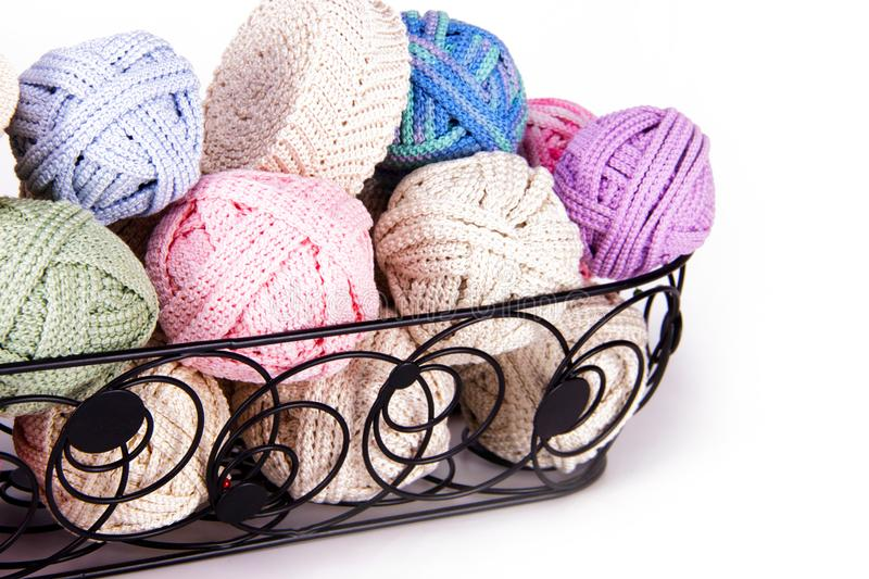 Black metal basket filled with Romanian Point Lace Macrame crochet cords in various colors to be used make tablecloth and doily cr. Aft protects stock photo