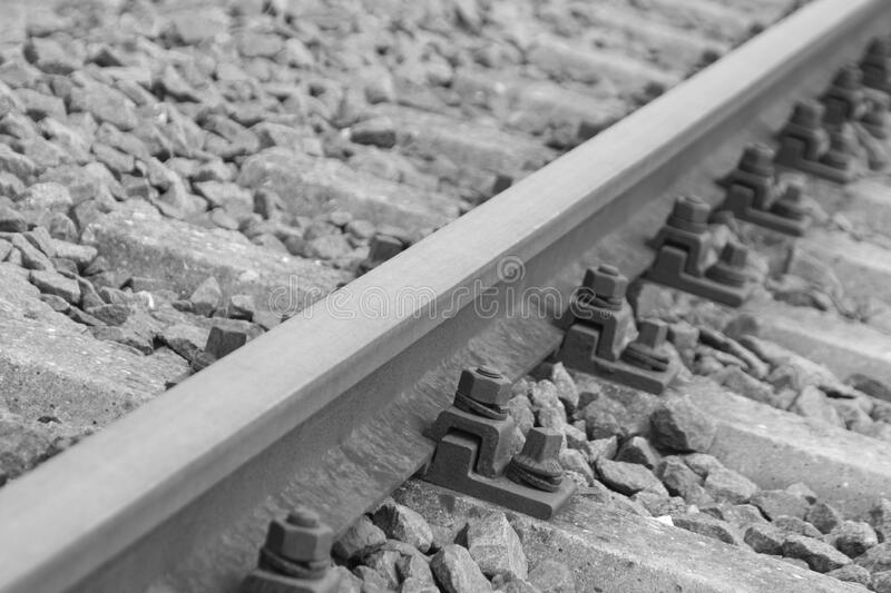 Black Metal Bolts in Silver Metal Train Rail Track Surrounder by Gray Stones stock image