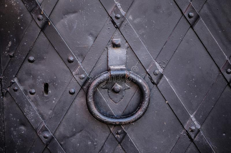 Black metal castle door. With a doorknob and key hole made out of cast iron royalty free stock images