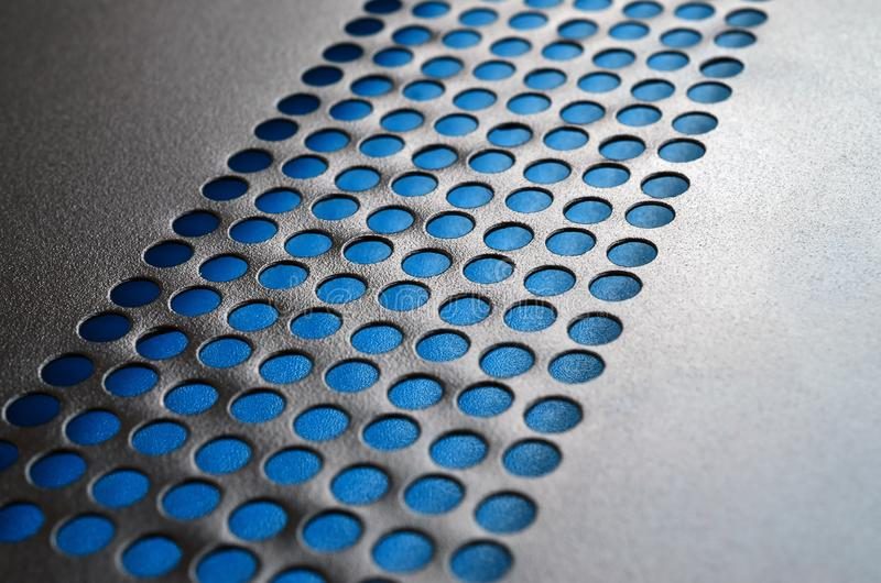 Black metal computer case panel mesh with holes on blue backgrou stock image