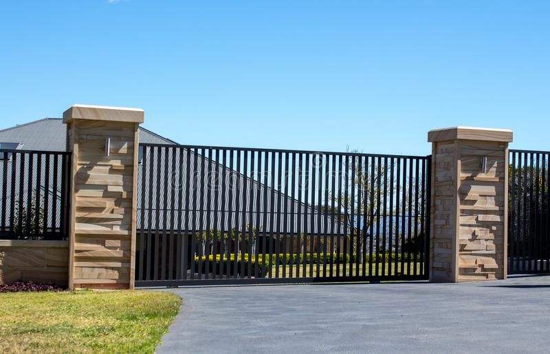 Black metal driveway entrance gates set in sandstone brick fence with residential garden. In background stock image