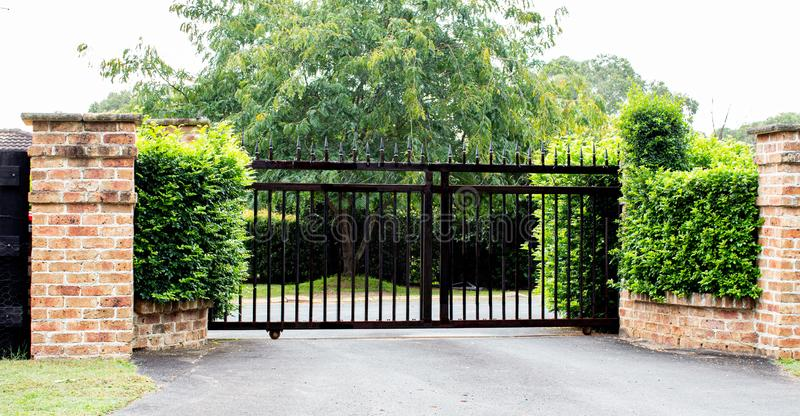 Black metal driveway property entrance gates set in brick fence with garden shrubs and trees in background. Black metal driveway security property entrance gates royalty free stock photo