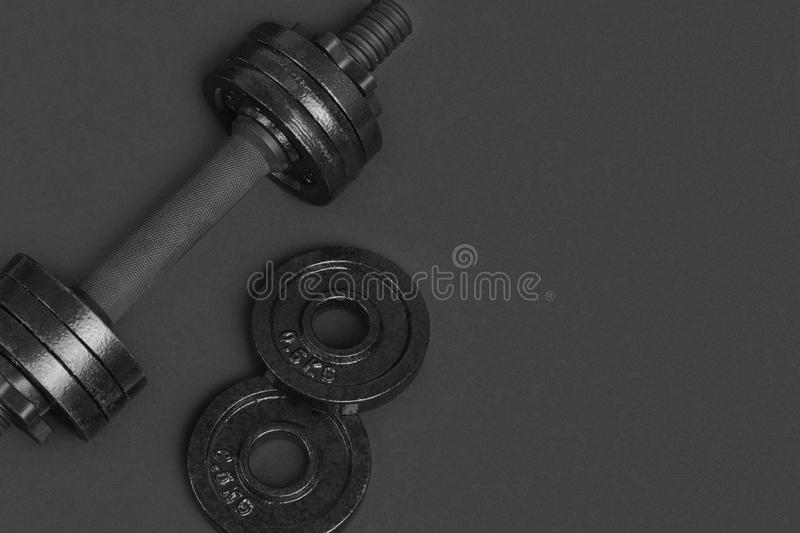 Black metal dumbbell for fitness on grey background stock photo