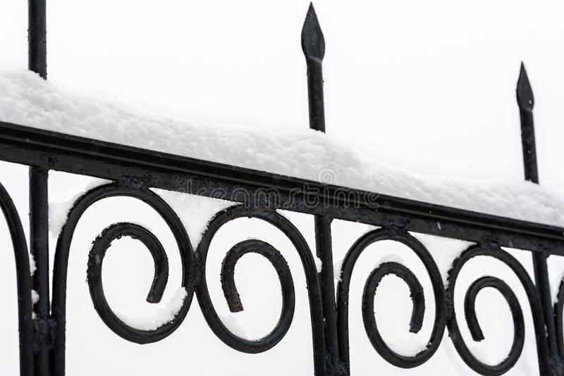 Black metal fence. Closeup. Snow on fence stock photography