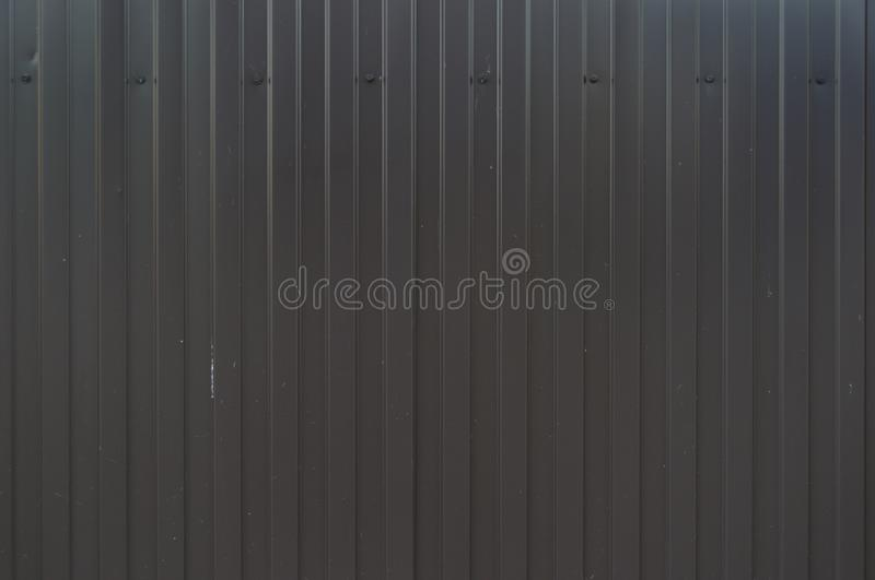 Black metal fence. Corrugated sheet or profiled sheet. Front. Metallic background. Striped textured backdrop. Brown Iron Way. The. Color of indigo stock photography