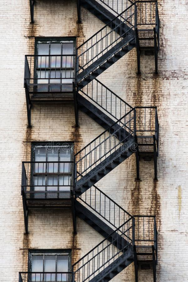 Black Metal Fire Escape Stairs Zig Zag and Connect Windows on the Way Down. The side of a weathered building royalty free stock photo