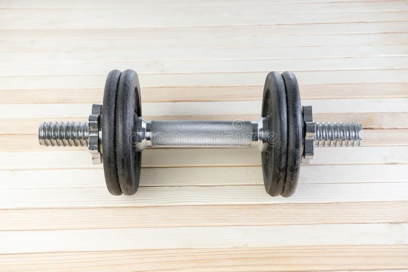 Black metal gym dumbbell with chrome silver handle on wood background with high resolution. fitness and weight loss concept royalty free stock images