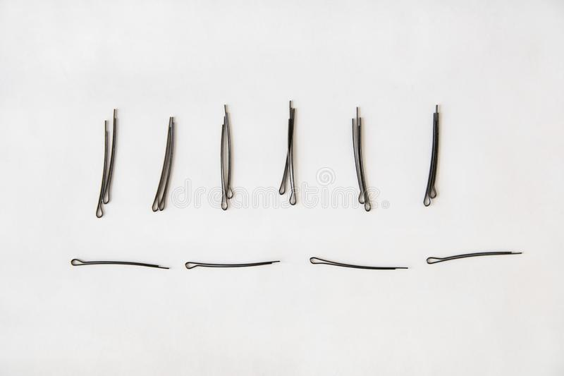 Black metal hairpins lie horizontally and exactly on a white background. Black metal hairpins lie horizontally and vertically exactly on a white background stock photography