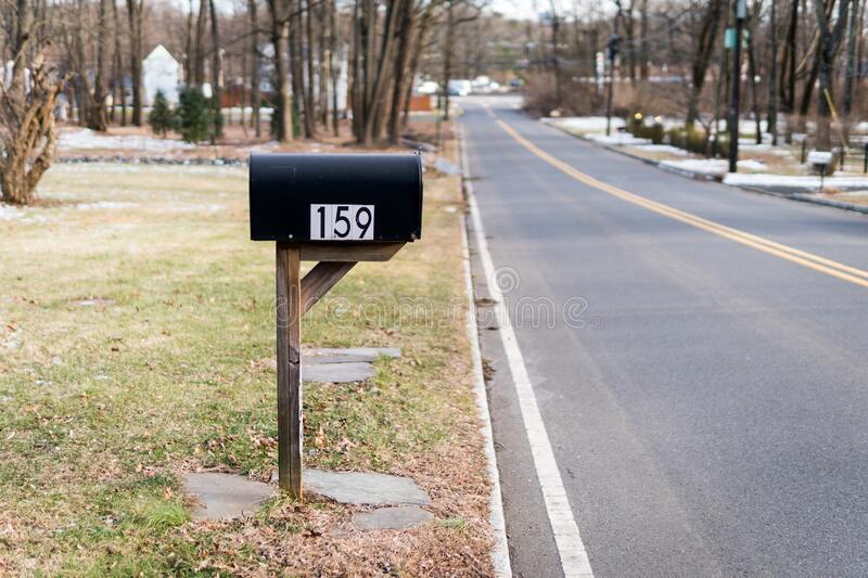 Black metal mailbox number 159 before Glenside Ave in Scotch Plains, New Jersey. Empty street. Cold winter. No traffic, no cars. Typical mailbox found at the stock photos