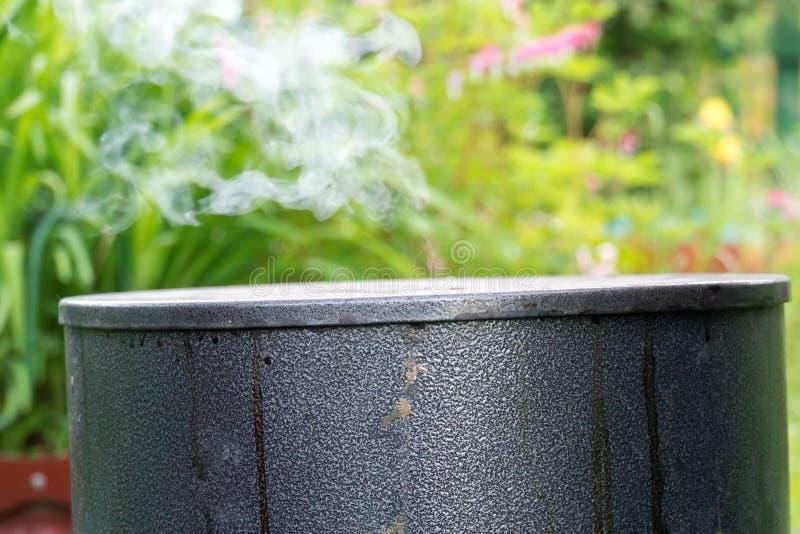 Black Metal Smokehouse. White smoke coming out from black metal smokehouse in the garden stock photo