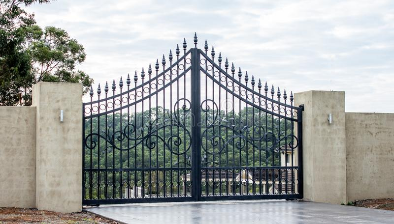 Black metal wrought iron driveway property entrance gates set in concrete brick fence, lights, garden trees in background. Black metal wrought iron driveway royalty free stock photography