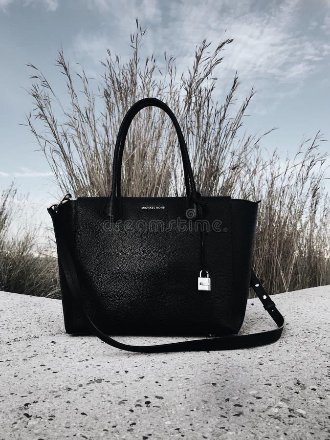 Black Michael Kors Leather 2-way Bag on Gray Surface royalty free stock photos