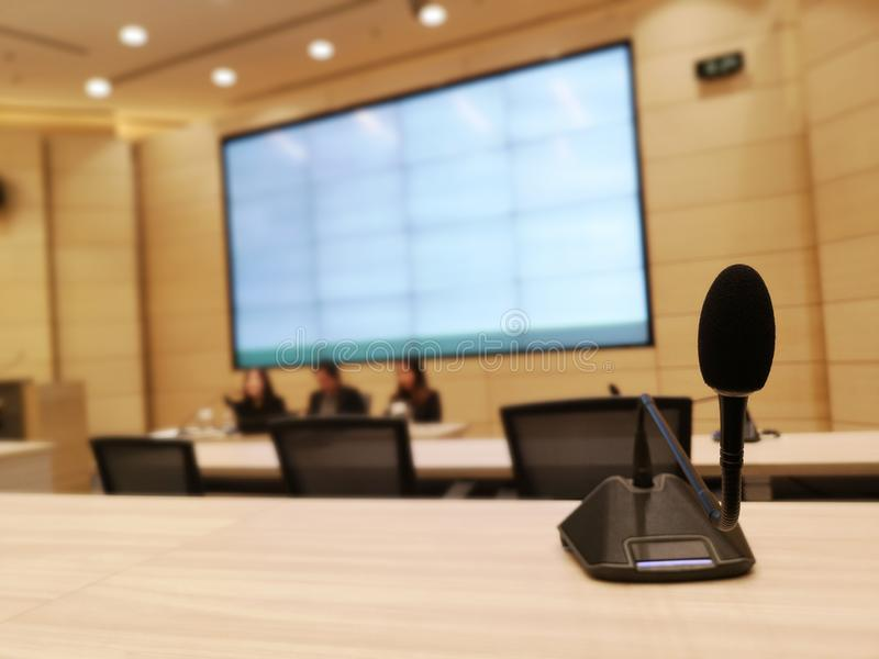 Black microphone in concert hall or conference meeting room or auditorium with defocused bokeh lights in background royalty free stock photo