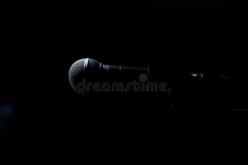 Black microphone on dark background. Black classic microphone on black dark background. Music and concert concept stock images