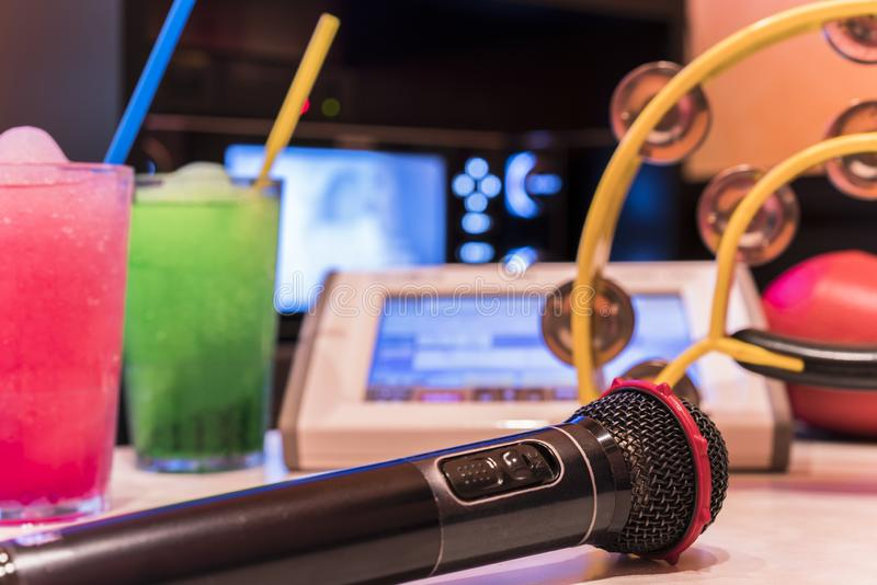 Black microphone in karaoke club, with remote controller, melon. And strawberry soda drinks, yellow tambourine and screen for singing music on stage party royalty free stock image