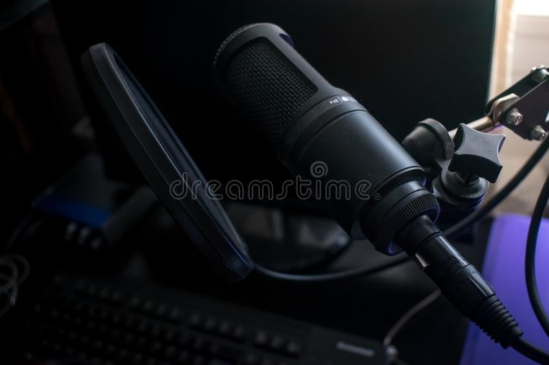 Black Microphone in home recording studio with pop shield on mic stand. Closeup Black Microphone in home recording studio with pop shield on mic stand royalty free stock image