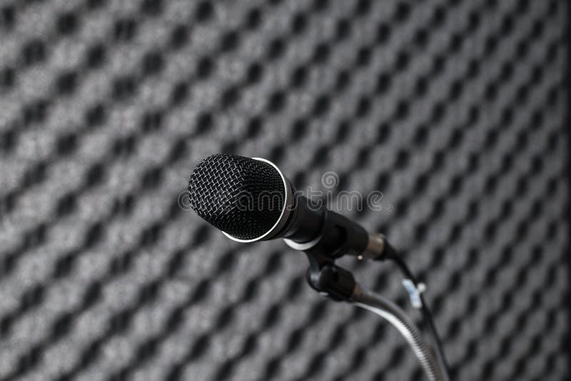 Black microphone in studio booth. Closeup of black microphone in studio booth royalty free stock photo
