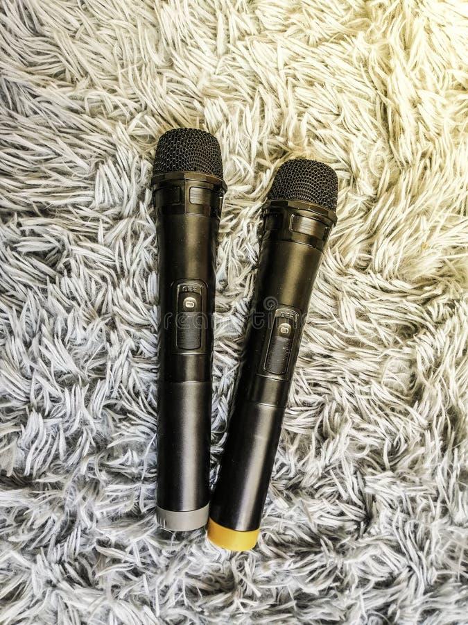 Black microphone on white carpet stock image