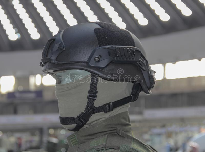 Black military combat helmet on the green doll and blurry background. Black military combat helmet on the green doll and blurry background stock photography