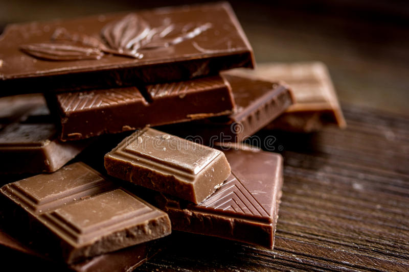 Black and milk chocolate pieces wooden table background royalty free stock photography